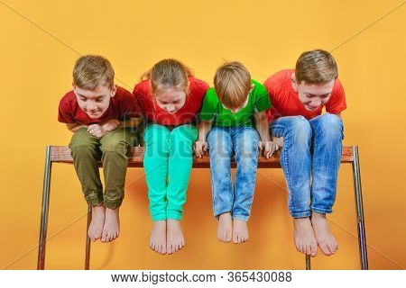 The Four Children Are Sitting Barefoot, Hanging Their Legs And Leaning Down Looking Down