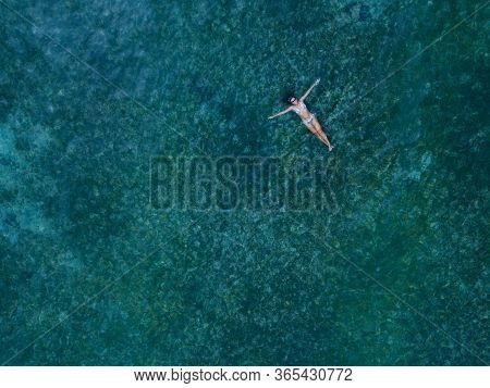 Woman In Bikini Lying On A Turquoise Ocean Water. Tropical Vacation Aerial Shot