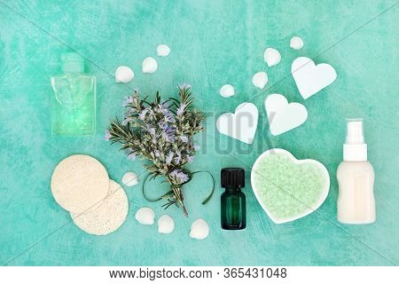 Skin care vegan beauty treatment with fresh rosemary herb and cosmetic beauty products. Has astringent & anti ageing benefits & helps to reduce environmental skin damage. Flat lay on turquoise.