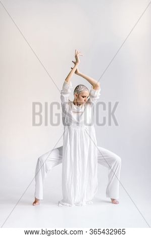 Woman In White Standing On Tiptoes Stretching Out Arms