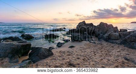 Idyllic Sunset On The Sea Shore. Waves Crashing Rocks On Sandy Beach. Beautiful Cloudscape Above The