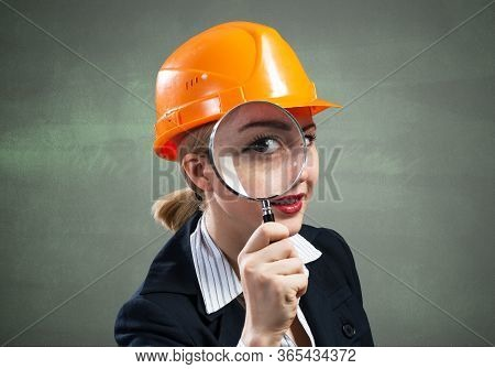Professional Appraiser Looking Through Magnifying Glass. Woman Civil Engineer In Safety Helmet Check