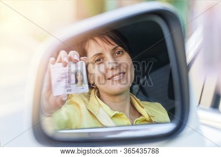 Getting A Driver's License, A Beautiful Driving Girl Shows A New Driver's License. Young Woman Holdi