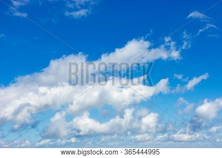 White Fluffy Clouds On The Blue Sky. Beautiful Nature Background