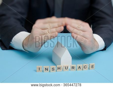 On The Table Is A Model Of A House, A Man In A Suit With His Own Hands Covers A Model Of A House. Th