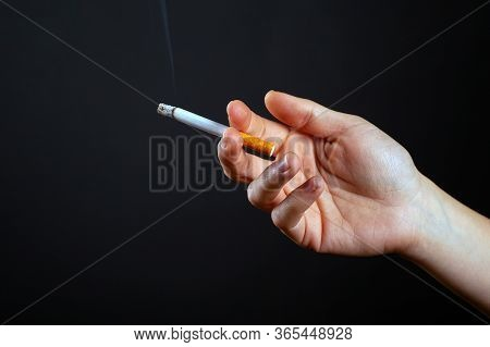 Female Hand Holding A Smoking Cigarette On A Dark Background Harm From Use Nicotine Close-up.