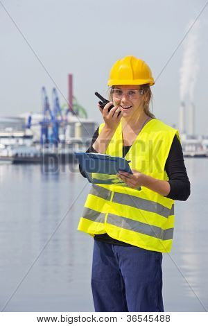 Happy female engineer communicating on a wireless radio, holding a clipboard with notes, wearing a hard hat, safety goggles and a reflective vest for safety