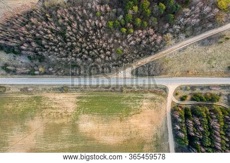 Aerial View Of Country Road Between Forest And Green Field. Spring Rural Landscape