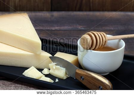 Macro Image Of Two Wedges Of Parmesan Cheese With A Cut Chunk. A Bowl Of Honey With Dipper On The Si