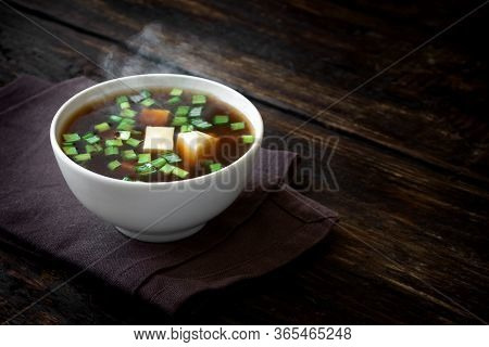 Miso Soup In  Bowl On Dark Wooden Background, Copy Space. Fresh And Steaming Japanese Miso Soup With