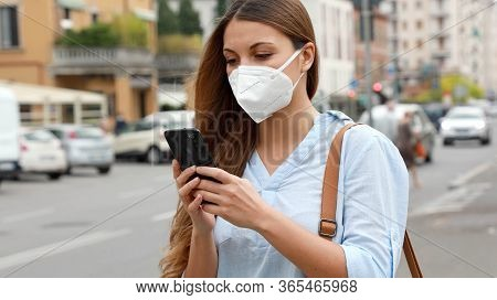 Covid-19 Young Woman Wearing Kn95 Ffp2 Mask Using Smart Phone Application Software In City Street To