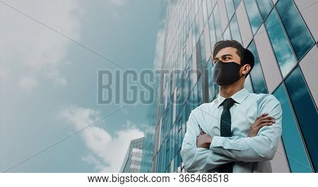 Covid-19 Situation In Business Concept. Businessman With Safety Mask Standing In The City. Protected