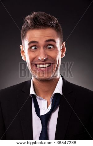Young businessman with tie undone, making a silly face.Cross eyed young businessman with mouth up to his ears. On black background