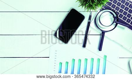 Top View Of White Desk With Computer Pen, Magnifier Graph.