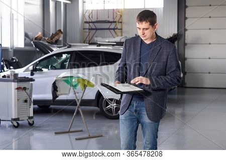 Manager Working In Auto Repair Shop With A Car On Background