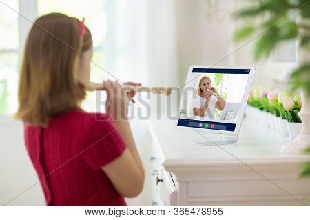 Child Playing Flute. Remote Learning From Home. Arts For Kid. Little Girl With Musical Instrument