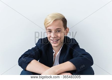 Close-up Of Teen Boy With Braces On Teeth Smiling On White Background. Dentistry And Teenager Concep