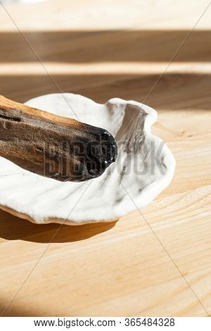 Peruvian Palo Santo Wood On A White Self-made Ceramic Plate With A Shape Of A Shell. Sand Colored Ta