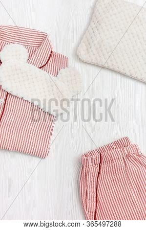 Sleepwear For Slumber. Pink Women Pajama With Stripes, Shirt And Shorts. Sleeping Mask On White Wood
