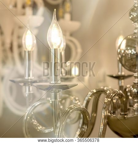 The Photography Of A Glowing Chandelier With Metal Chrome Fixtures And Shades In The Form Of Candles