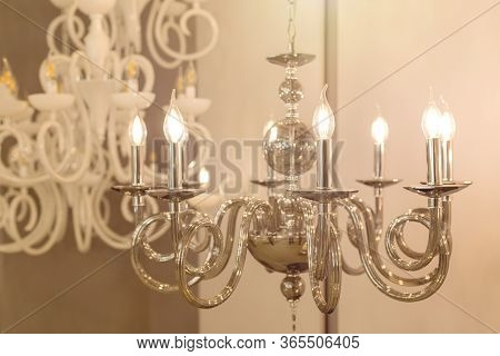 The Image Of A Glowing Lamp With Metal Chrome Fixtures And Shades In The Form Of Candles. The Concep