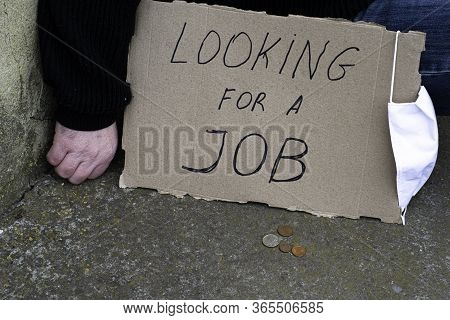 Unemployment Concept And Unemployed Coronavirus Sitting On The Ground Next To It A Cardboard Plate W