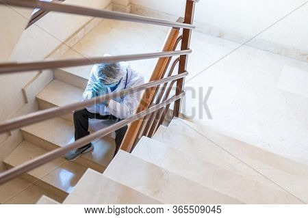 Doctor Sitting On Hospital Stairs Disappointed After Surgery Results.