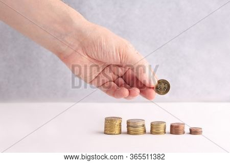 Hand Put Money Coins To Stack Of Coins On A White Background. Invest Your Money To Get In Come, Grow