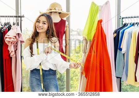 Portrait Of Asian Woman Fashion Designer Standing Smiling With Holding Show Tape Measure At The Desi