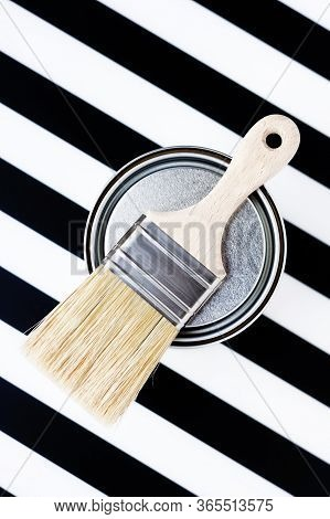 Paint Metal Round Can And New Brush On Black And White Background. Focus On Brush. House Renovation.