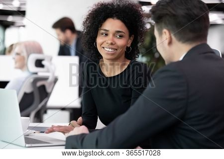 Multiracial Coworkers Discussing Work Moments Seated In Co-working Space