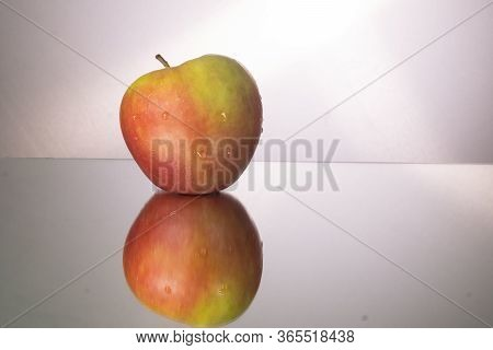 Red Apple On Mirroring Table. Gorizontal Image With Copy Space.