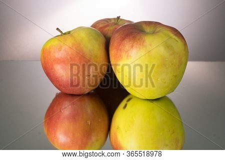 Three Red Apple On Mirroring Table. Gorizontal Image With Copy Space.