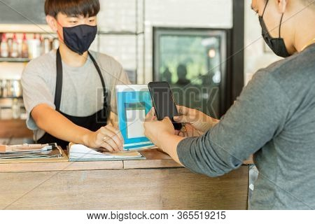 Male Customer With Protective Mask Paying Bill By Cell Phone In Cafe