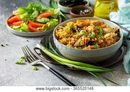Bulgur Pilaf. Healthy Eating Concept. Bulgur With Chicken, Vegetables And Prunes On A Gray Stone Or