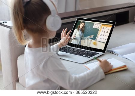 Distance Learning. Cheerful Little Girl Girl In Headphones Using Laptop Studying Through Online E-le