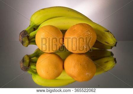 Yellow Bananas And Oranges On Mirroring Table. Gorizontal Image