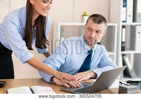 Sexual Harassment. Female Boss Harassing Male Employee Seducing Touching His Hand Working Together A