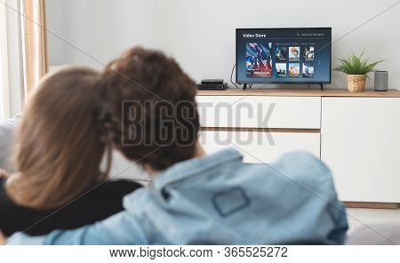 Couple Watching Tv On Sofa. Television, Multimedia, Video On Demand Service