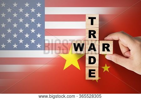 Hand Putting Trade War Wording On Usa And China Flag.it Is Symbol Of Tariff Trade War Tax Barrier Be