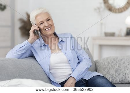 Positive Senior Woman Talking With Friend On Cell Phone, Sitting On Couch At Home, Resting In Living