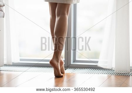 Woman Standing Tiptoes Barefoot On Warm Floor Closeup Image