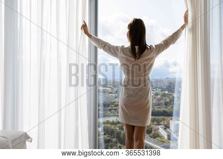 Rested Female Wakeup Opens Curtains Enjoys City And Sunny Weather