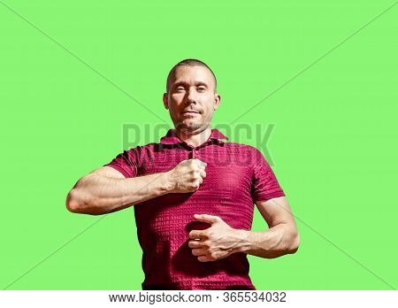 A Smug Man Hits His Chest With A Fist On A Green Background