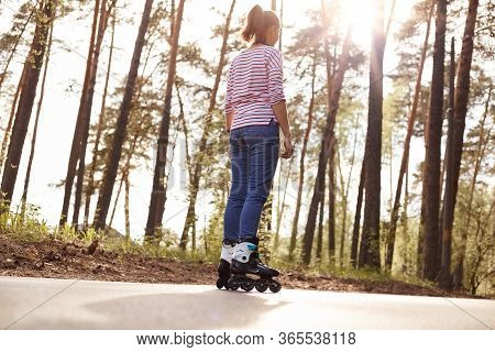 Back View Of Female Dresses Casual Attire Rollerblading Outdoors, Spending Her Free Time In Forest,
