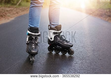 Horizontal Picture Of Unknown Person Rollerskating, Rollerskates Being On Wet Road, Having Sun On Ba