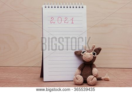 The Bull Is The Symbol Of The New Year 2021. A Knitted Toy Bull Next To A Blank Notepad On A Wooden