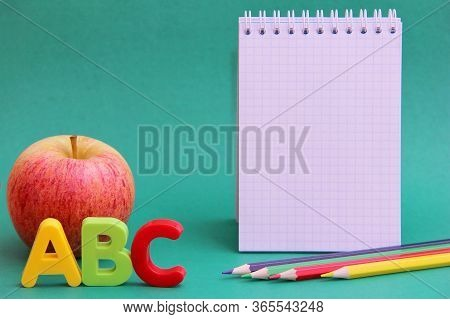 English Abc Alphabet Letters Next To Apple. Colored Pencils And An Empty Notepad Page Learning Forei