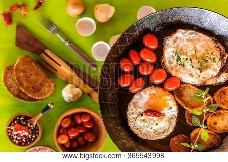 Fried Eggs In A Frying Pan With Cherry Tomatoes And Bread For Breakfast . Fried Potatoes And Tomatoe