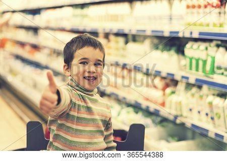 Happy Boy 4 Years In A Supermarket On The Background Of Shelves With Milk And Yogurt. The Boy Showed